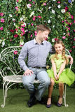 Happy father looks at little daughter sitting on retro bench Stock Image