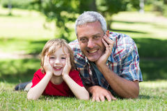 Happy father lying on the grass with his son Stock Photography