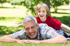 Happy father lying on the grass with his son Royalty Free Stock Photos