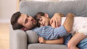 Happy father lying on sofa hugging kid rest cuddle together. Happy father lying on sofa hugging cute little girl rest on comfortable couch, loving caring dad stock video footage