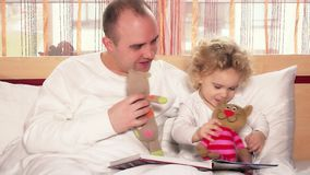 Happy father man playing with lovely daughter girl using toy cats. Static shot. 4K UHD stock footage
