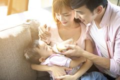 father and mother feeding baby from bottle royalty free stock photos