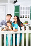 Happy father, mother and little daughter stand next to fence Royalty Free Stock Photos