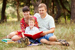 Happy father, mother and son reading book. On the lawn in the park. Family reading together royalty free stock images