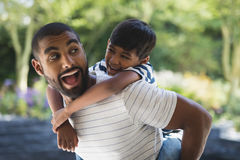 Happy father piggybacking his son at porch Royalty Free Stock Images