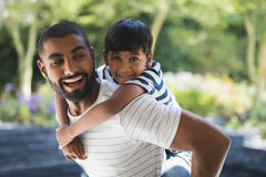 Happy father piggybacking son at porch Stock Images