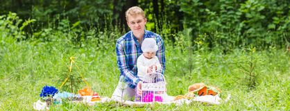 Happy father play with adorable little baby daughter in nature stock photo