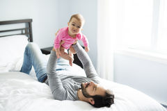 Happy father playing with adorable baby in bedroom. A happy father playing with adorable baby in bedroom Stock Image
