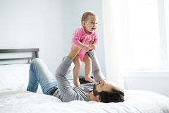Happy father playing with adorable baby in bedroom. A happy father playing with adorable baby in bedroom Royalty Free Stock Photos