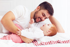 Happy father playing with adorable baby in bedroom Royalty Free Stock Photography