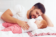 Happy father playing with adorable baby in bedroom Stock Image
