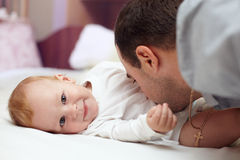 Happy father playing  with baby in bed. Young happy father playing  with baby. Man and baby are lying in bed. baby want to catch father's face Royalty Free Stock Photos