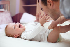 Happy father playing  with baby in bed. Young happy father playing  with baby. Man and baby are lying in bed. baby want to catch father's face Stock Photo