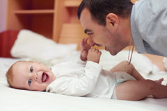 Happy father playing  with baby in bed. Young happy father playing  with baby. Man and baby are lying in bed. baby want to catch father's face Stock Images