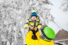 Happy family during the winter vacations. Happy father playing with baby boy standing in winter spots clothes outdoors during the winter vacations royalty free stock photos