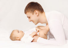 Happy father playing with baby at home lying on the bed Stock Photos