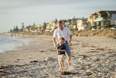 Happy father playing on the beach with little son running excited with barefoot in sand and water Stock Images