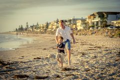 Happy father playing on the beach with little son running excited with barefoot in sand and water Stock Photo