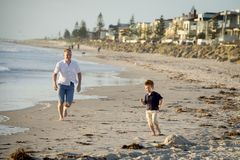 Happy father playing on the beach with little son running excited with barefoot in sand and water Royalty Free Stock Images