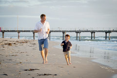 Happy father playing on the beach with little son running excited with barefoot in sand and water. Young happy father playing on the beach with little son Royalty Free Stock Photo