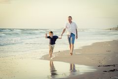 Happy father playing on the beach with little son running excited with barefoot in sand and water. Young happy father playing on the beach with little son Stock Photography