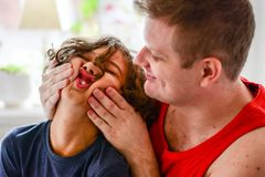 Happy father playing with boy in kitchen. Funny faces happy days Royalty Free Stock Photography