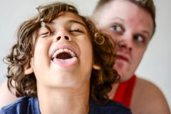 Happy father playing with boy in kitchen. Funny faces happy days Stock Images