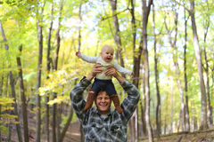 Happy Father Playing with Cute Baby daughter in Autumn Woods Stock Images