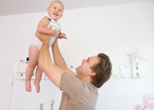 Happy father playing with cute baby at home Stock Photos