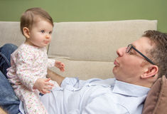 Happy father playing with cute baby in a sofa Stock Image