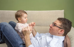 Happy father playing with cute baby in a sofa Stock Photography