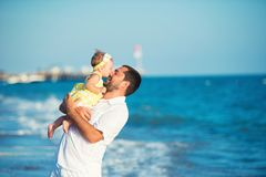 Happy father playing with cute little daughter at the beach stock photography