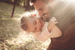 Happy father playing with daughter in park and hugging h. Smiling happy father playing with daughter in park and hugging her royalty free stock image
