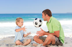 Happy father playing football with his son. At the beach royalty free stock photography