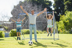 Happy father playing football with his son and daughter. At the park Stock Images