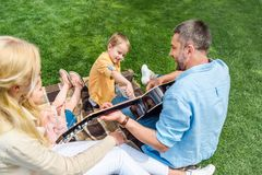 Happy father playing guitar while spending time with family. In park royalty free stock photos