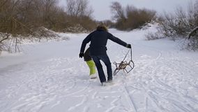 Happy father playing with his son sledge. Together they rejoice and be glad in natural rink. Boy catching sleigh. Slow stock video