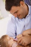Happy father playing with little daughter smiling Stock Photo