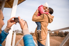 Happy father playing with little daughter. Young women photographing happy father playing with adorable little daughter at sunny autumn day Royalty Free Stock Photos