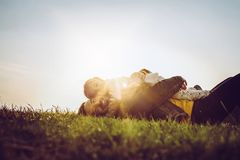 Happy father playing and lying on grass with his daughter. Looking at camera. royalty free stock photo