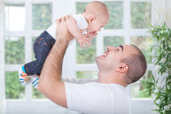 Happy father playing and smiling with his son Stock Photos