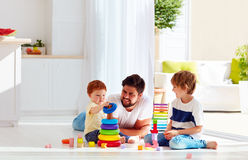Happy father playing with sons at home. Happy father playing with sons on the floor at home stock image