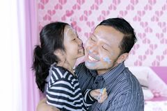Happy father playing together with daughter. Picture of happy father kissed by his daughter after playing with face painting in the bedroom Royalty Free Stock Image