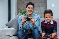 Happy father playing video games with his son Stock Photos