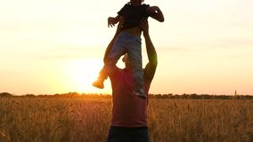 A happy father plays with a child in a wheat field at sunset. Dad throws his son up. Emotions of joy, happiness, fun.