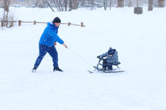 Happy father plays with little son on snowracer Royalty Free Stock Images
