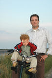 Happy Father, Pouting Child. Father and son on a bicycling tour along the coast at sunset. Father is happy and content, but the young son is angry and pouting Stock Photo