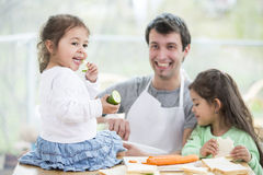 Happy father preparing sandwiches while daughters eating at home Stock Photos