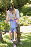 Happy father pushing boy on swing Stock Photos