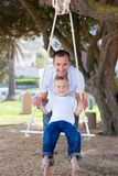 Happy father pushing his son on a swing. In a park Royalty Free Stock Photography